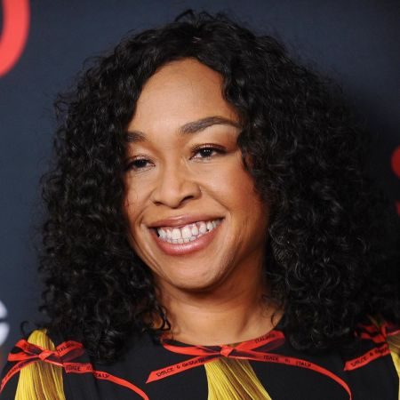 Shonda Rhimes in a black dress poses for a picture.