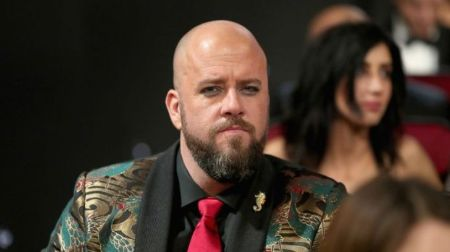 Chris Sullivan poses at an event in his stylish suit.