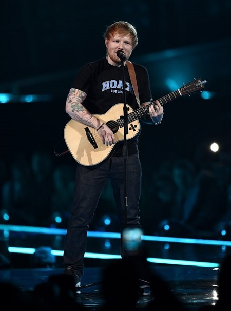 Ed Sheeran on stage in front of the mic with a guitar in his hands.