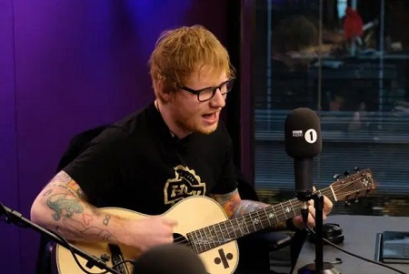 Ed Sheeran playing the guitar during the radio show.