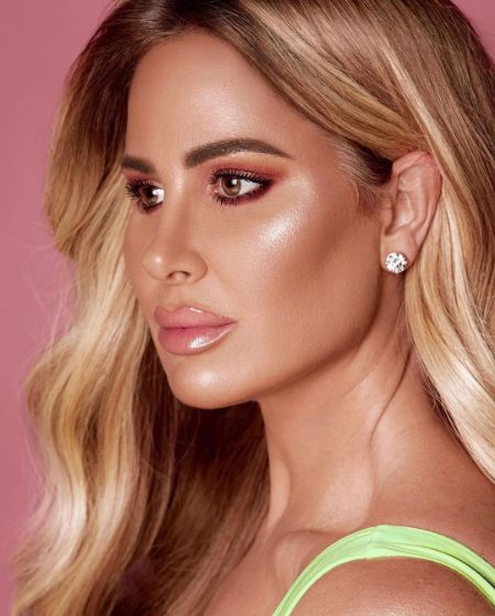 Kim Zolciak in a green top poses for a photoshoot.