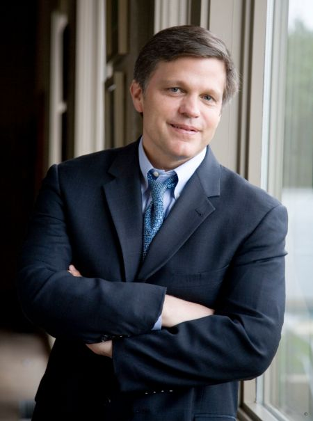 Douglas Brinkley in a black suit and blue tie poses for a picture.