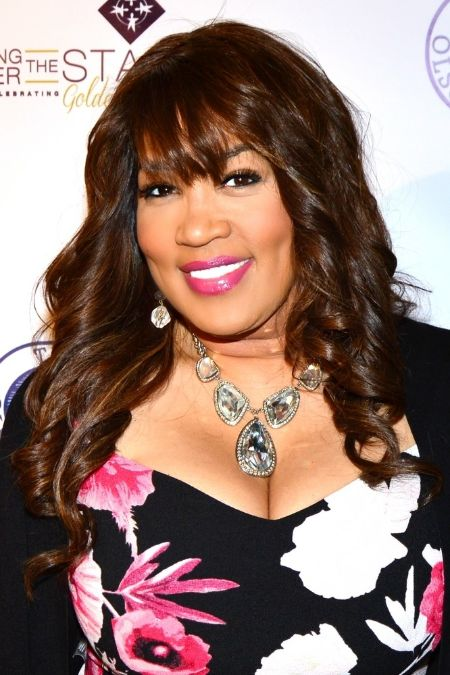 Kym Whitley in a black dress poses for a picture.