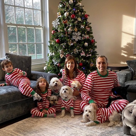 Joe Gatto with his wife Bessy Gatto, their two kids and five dogs in front of a Christmas tree.