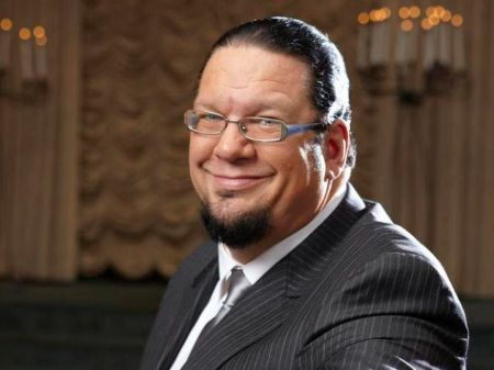 Penn Jillette in a black suit smiles at the camera.